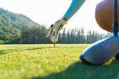 Fotografie Hand des Golf Spielerin sanfte abschrecken einen Golfball auf hölzernen Abschlag am Tee, um zu machen bereit Hit vom Abschlag, Fairway Ahea aus