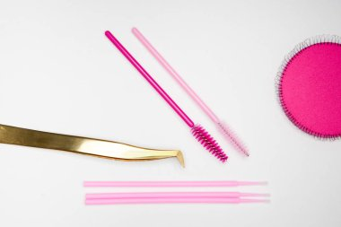 tools for eyelash extension, golden tweezers, pink brushes on a white background