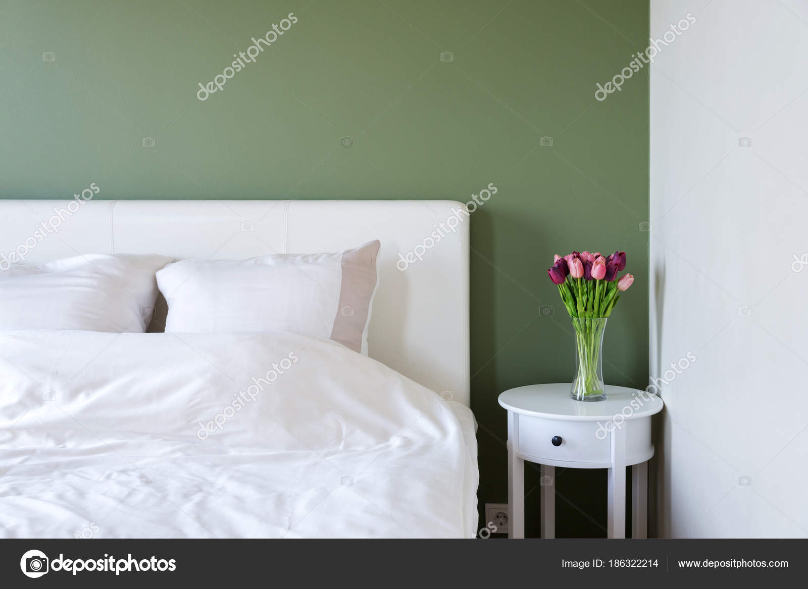 Schlafzimmer Innenraum mit weißen Bett und Nachttisch mit Blumen ...
