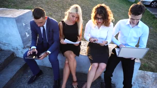Business Team Sitting Near Center Office With Documents, Laptop, Tablet Technology Against Sun
