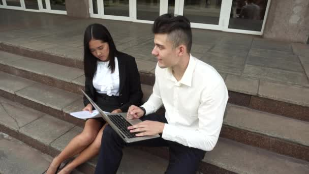Young Beautiful Business Woman Female and Caucasian Male Use Documents, Laptop Press Keyboard Sit on Office Building Stairs