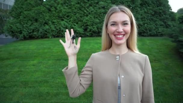 Mladá krásná Blond žena v ruce drží klíče od domu byt byt Estate se těší