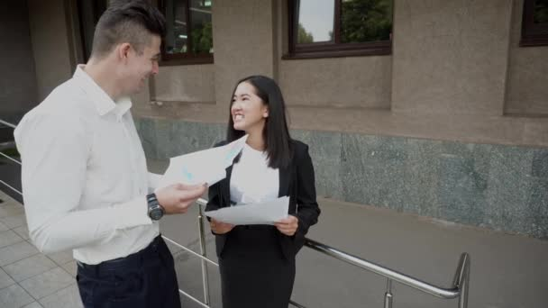 Young Beautiful Asian Business Woman Female and Caucasian Male Look at Documents Talk on Office Building Background