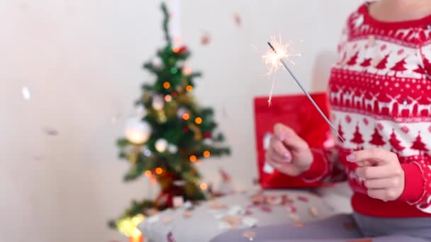 Young Girl Uses Hand Hold Sparklers, Bengal Fire Christmas Tree on Bokeh Xmas Eve Lights New Year Tree Confetti