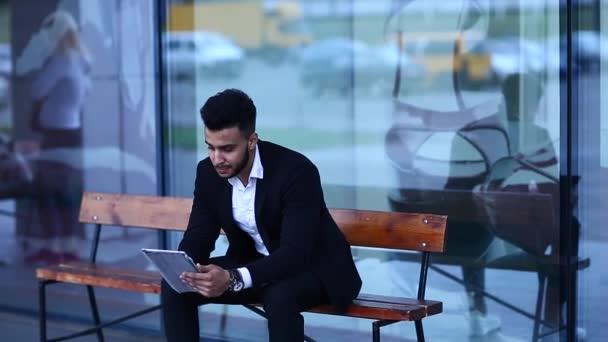 Muž v obleku, Arabština uvádí na sluneční brýle s tabletem v okolí