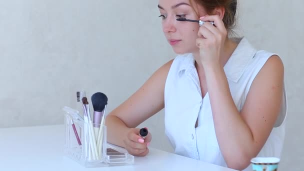 Brush For Make up in Girls Hand in White Room Doing Makeup Shadows