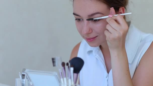 Štětec na make-upu v rukou dívky v bílém pokoji dělá make-up