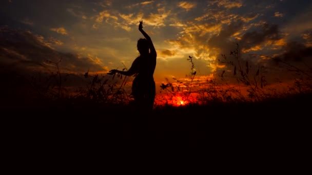 Silhouette Against Red Orange Sunset of One Young Graceful Girl Practicing Yoga Outdoors.