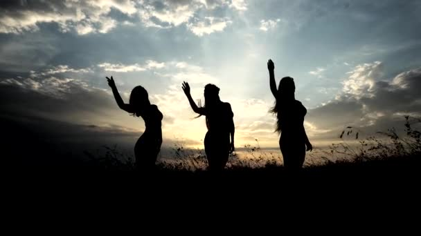 Silhouettes Against Sunset of Three Young Slender Girl Practicing Yoga Outdoors.