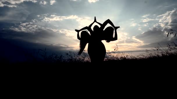 Silhouettes Against Sunset of Three Young Slender Girl Practicing Yoga Flower Outdoors.