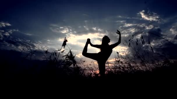 Silhouette Against Sunset of One Young Graceful Girl Practicing Yoga Outdoors.