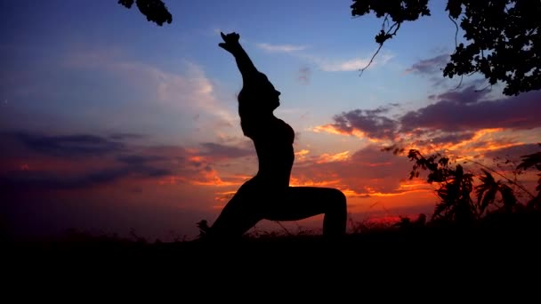 Silhouette Against Colorful Sunset of One Young Graceful Girl Practicing Yoga Outdoors.