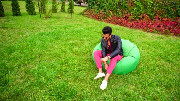 Arab chlap zamyšlené pohledy stranou, odpočinku a posezení v křesle v zelené zahradě