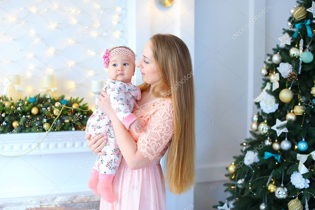 Young mother with daughter baby little girl smiling, posing and laughing in decorated Christmas studio on background wall with garlands, white fireplace and Christmas tree. Woman dressed in long pink