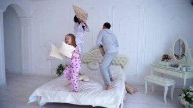 Portrét rodiny boj polštáře, skákání na posteli společně v pyžamu