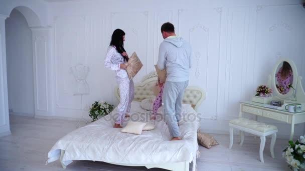Famiglia di salto e scherzare in letto, marito e moglie lotta di cuscini