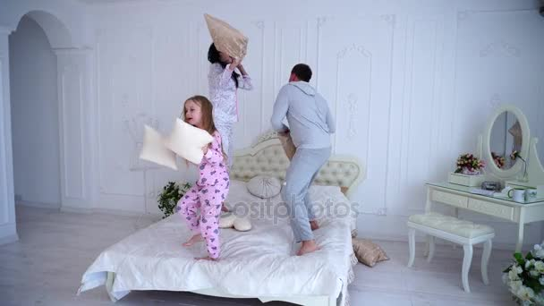 Portrait of Family Fighting Pillows, Jumping on Bed Together in Pajamas