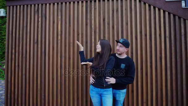 Pár v lásce líbání a objímání, šeptání a stát blízko zdi restaurace venku