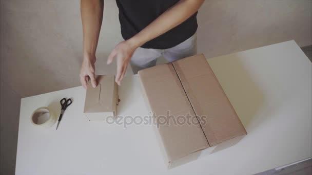Dopravce kontroly obědové boxy, utěsněné páskou na všech stranách, zapne a stanoví se na velké krabice malé pole v pošta