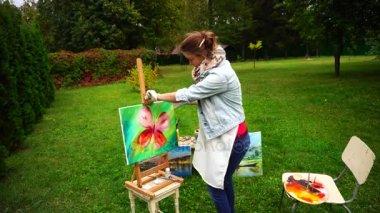 Művész nő tart festés és pózol a kamera és a mosoly, a szabadban állt teljes növekedés a háttérben, a fű és a fák, a Park