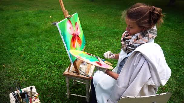 Művész lány felhívja, és csodálja a festés, és ül a szék-Park szabadban hűvös tavasz