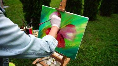 Káprázatos művész lány festék pillangó szárnyak Burgundia színes és a festőállvány a szabadban Park közelében áll