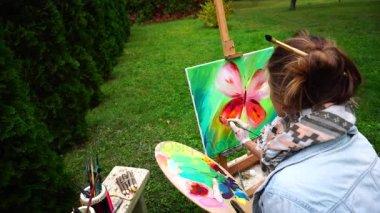 Művész lány felhívja a képet, és ül a székre Park kamera vissza szabadban őszi