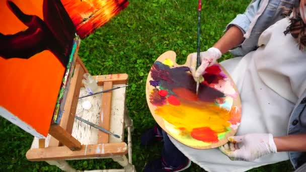 Women Artist Leads Brush on Palette and Mixes Color Against Background of Orange Picture and Sits on Chair in Park Outdoors.