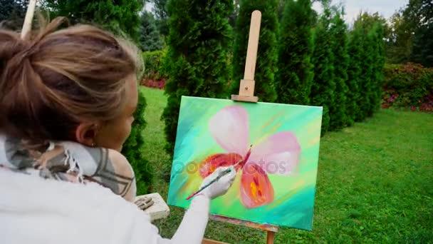 Elején a művész nő körvonalak pillangó szárnyak és ül a háttérben a tűlevelű fák szabadban Park kamera vissza a festőállvány