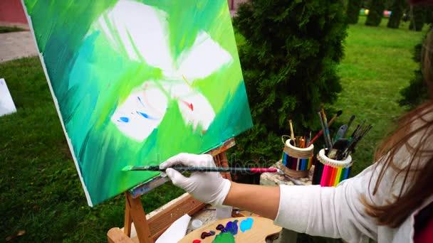 Csábító lány művész a háttér sorsolása zöld festés és ül a szék-Park szabadban hűvös tavasz