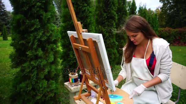 Nő a művész, hogy ül a festőállvány kamera és festékek vászon szabadban hűvös tavaszi napon portréja