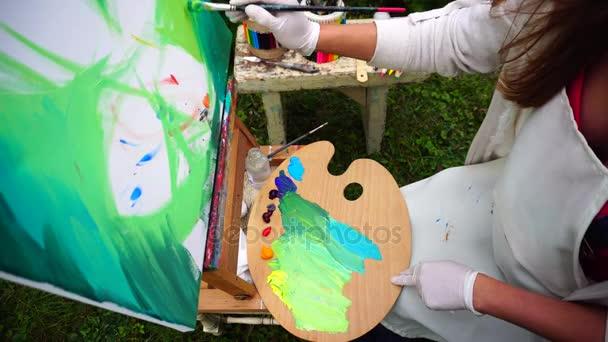 Iskolás művészeti iskola háttér festékek színek ecsettel a kezében tartja, és vezet a vászon, paletta tartja a lábát, és ül a parkban szabadban