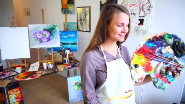 Ženy krásný malíř pózování a úsměv do kamery s štětce a palety v ateliéru ověšené skici a kresby.