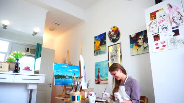 Girl Sits on Stool at Easel and Writing Painting With Uses Brush to Paint and Located in Bright Beautiful Art Studio.