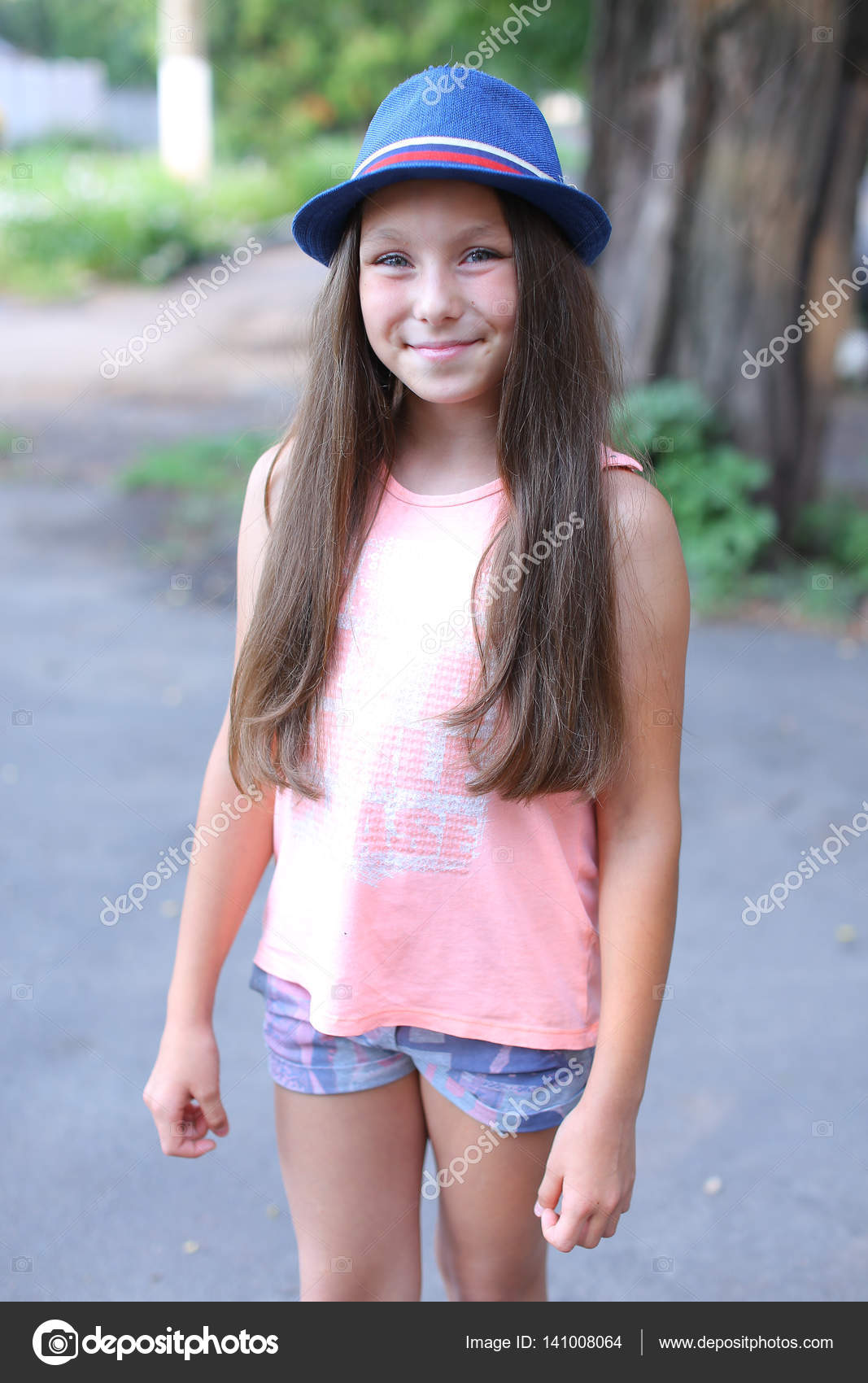 cute girl child smiling, looking at the camera and standing on s