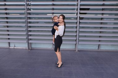 Beautiful modern girl, young mother, business woman squatted dow