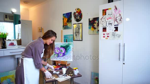 Roztomilá malá holka malíř barvy obrázek a příchozí hovor Smartphone, zabývající se dialogu a zápisy v poznámkovém bloku zpracovávat v bílé Art Studio.