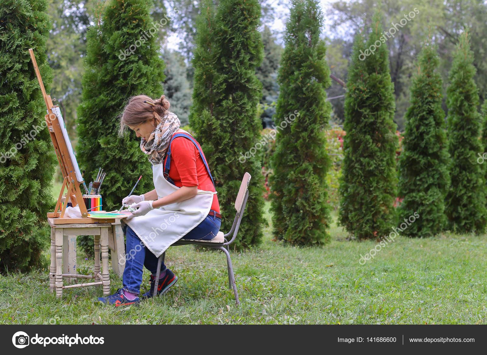 Mädchen-Künstler malt Bild und setzt auf Stuhl an Staffelei Seiten ...