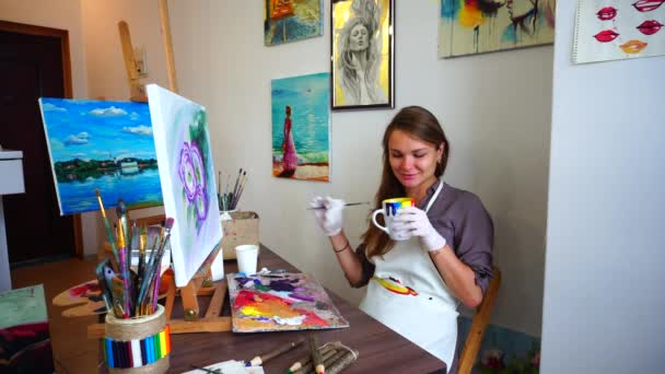 Young Artist Woman Takes Cup in Hands and Drank Drink, Sitting With Brush in Hand Near Complete Picture on Easel on Chair at Table in Studio.