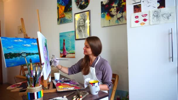 Women Artist Sits in Profile to Camera Dips Brush in Paint and Causing Strokes to Canvas With Brush, Sits Onchair at Easel in Art Class.