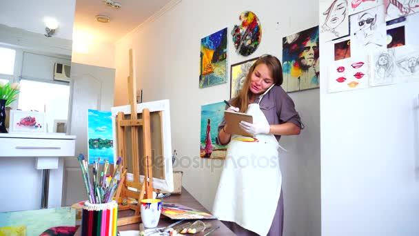 Okouzlující umělec udržuje rameno a mluví o telefonu, píše perem na podložce v ateliéru.