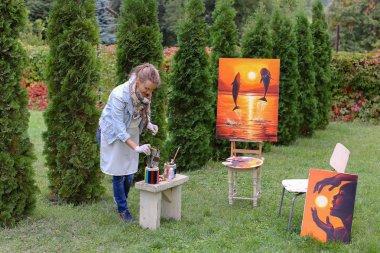 """Картина, постер, плакат, фотообои """"девушка стирает кисть и кладет в банк, глядя на картину, которая стоит картина"""", артикул 142601735"""