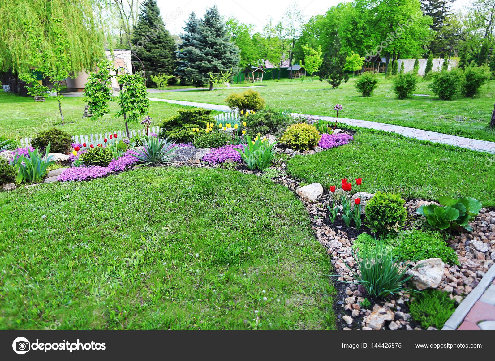 Landscaped area with green spaces, plants, flowers and trees