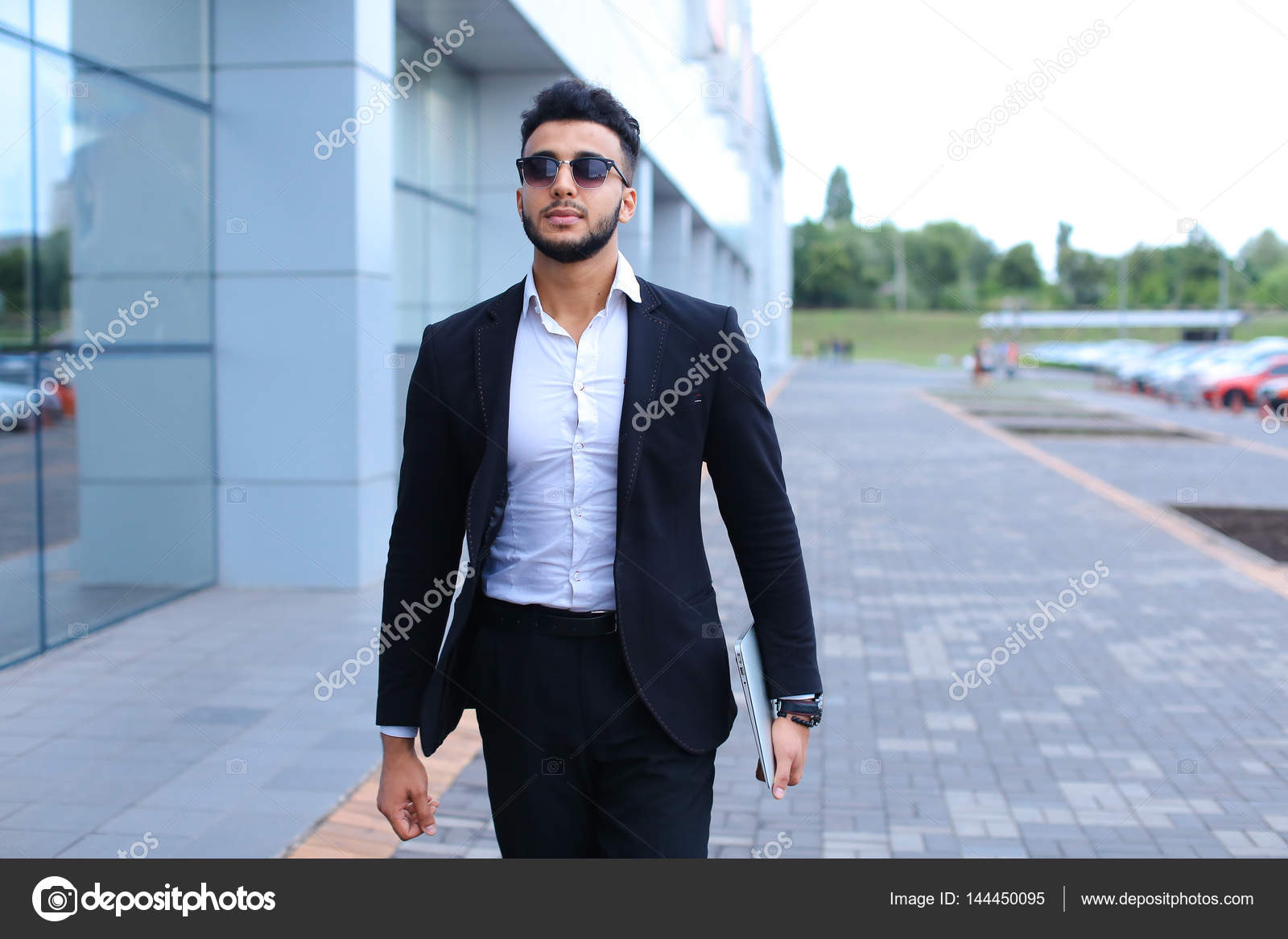 f377d1995fc Young handsome businessman Arab Muslims is in the business center in black  elegant dress on building background. Businessman man male looking at time  ...