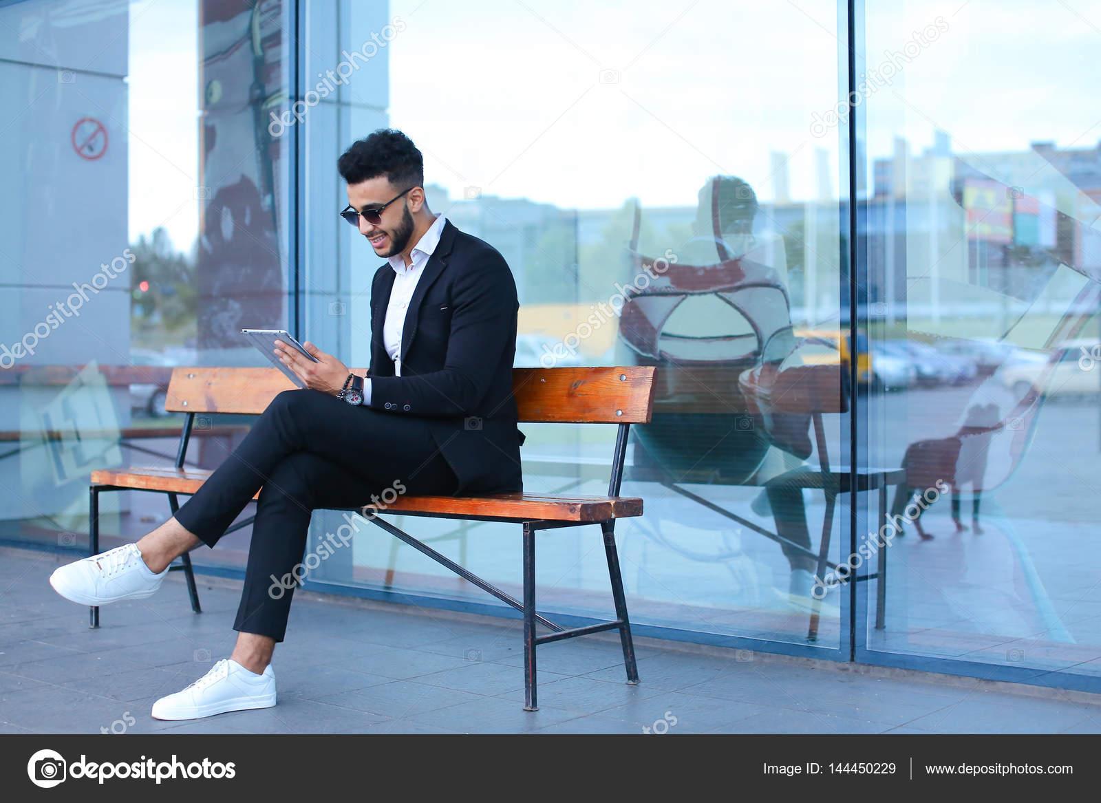Підприємець посміхаючись людина ставить планшетний ПК використовує сонцезахисні  окуляри і дивиться на. Красивий Молодий підприємець Арабські мусульман в ... b8c9f77571ca4