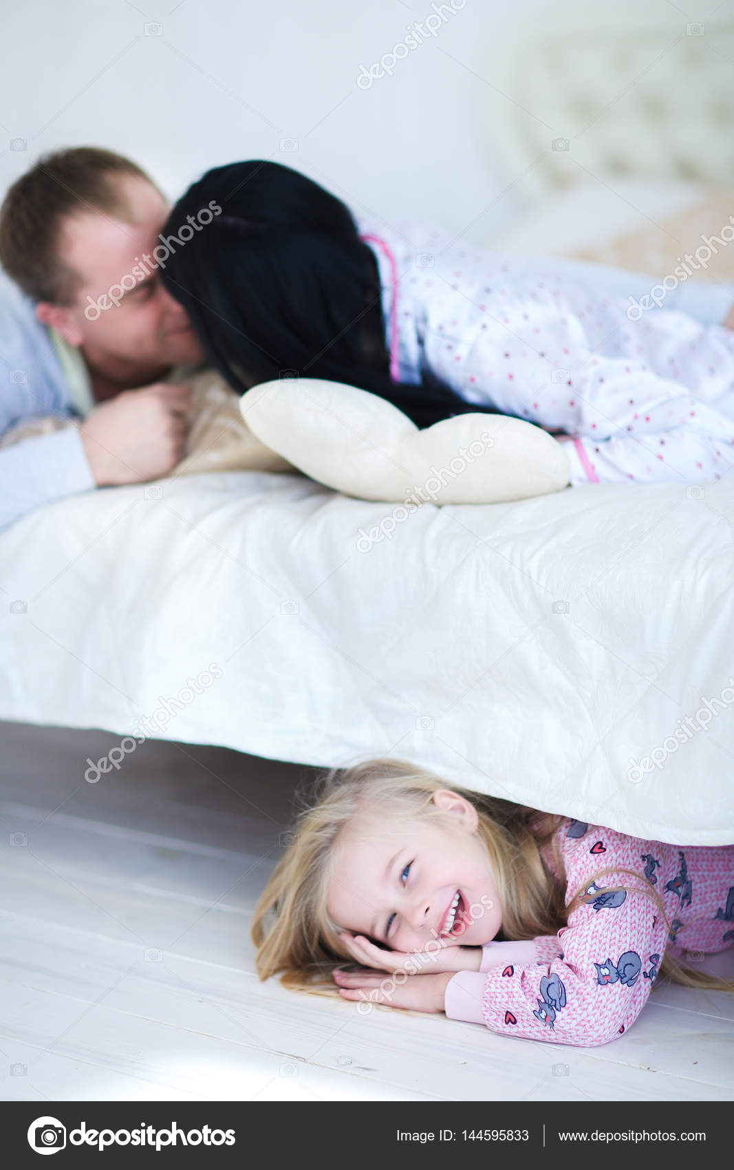Daughter Hiding Under Bed Mom And Dad Spoken At Home Stock Photo
