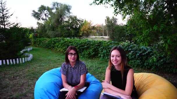 Successful Female University Students Posing, Smiling at Camera and Sitting in Park in Soft Chairs on Open Air During Summer Day.