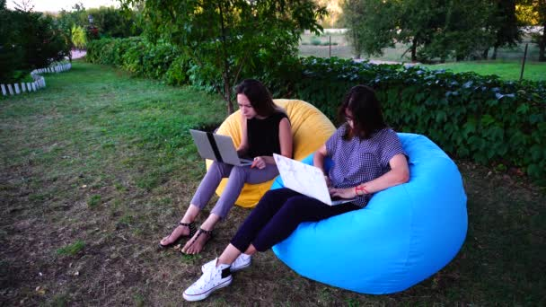 Educated Female University Students Type on Gadget Keyboard Course Project Sitting in Soft Outdoor Chairs on Summer Day.