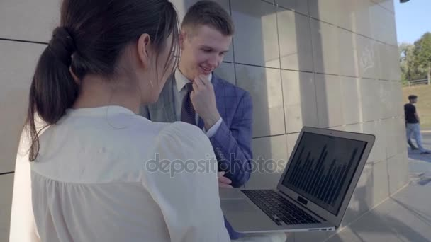 Two Girls and Boy Hold in Hands Laptop and Folders, Smiling and Looking at Camera on Background of Business Center Outdoors in Neutral Colors.