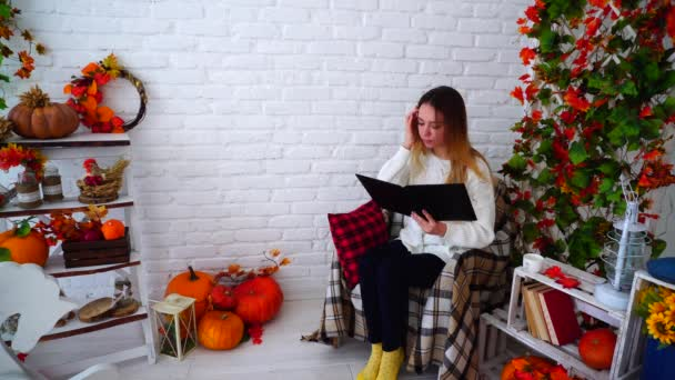 Female Student Holding Folder and Reading Homework, Sitting in Chair Against White Wall Decorated With Autumn Decorations in Room.